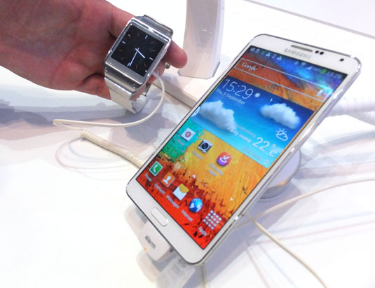 The Samsung Galaxy Gear poses next to the Samsung Note 3.