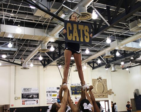 Junior Varsity cheerleader, Gaby Amaral, shows off her school spirit by holding up a school sign. This seems like a simple task, however, the flyer has to squeeze all her muscles to take pressure off the bases and hold on to the sign while getting catapulted into the air. This stunt not only pushes their bodies to the physical extreme but the idea of falling from the fullest extension is devastating. It takes hardwork and dedication to the team in order to pull off this stunt.